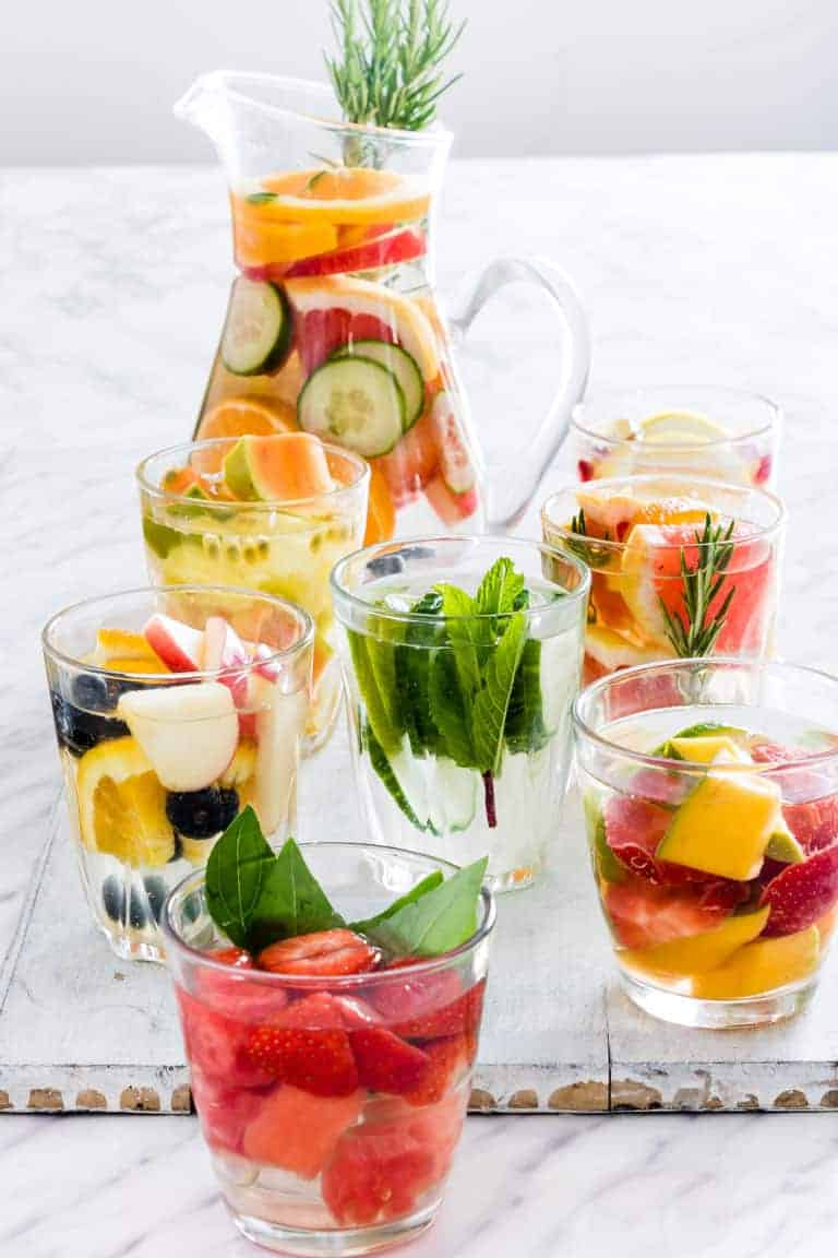 A table full of Infused water in a pitcher and 7 glasses. Full of fruits, vegetables and herbs