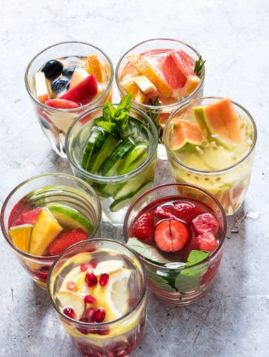 7 fruit infused water glasses on a grey tabel