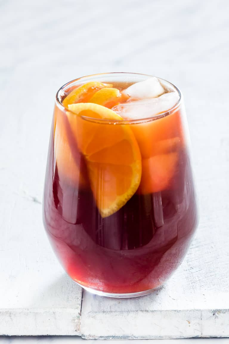 A glass of instant pot iced tea with clementines and ice on a white table