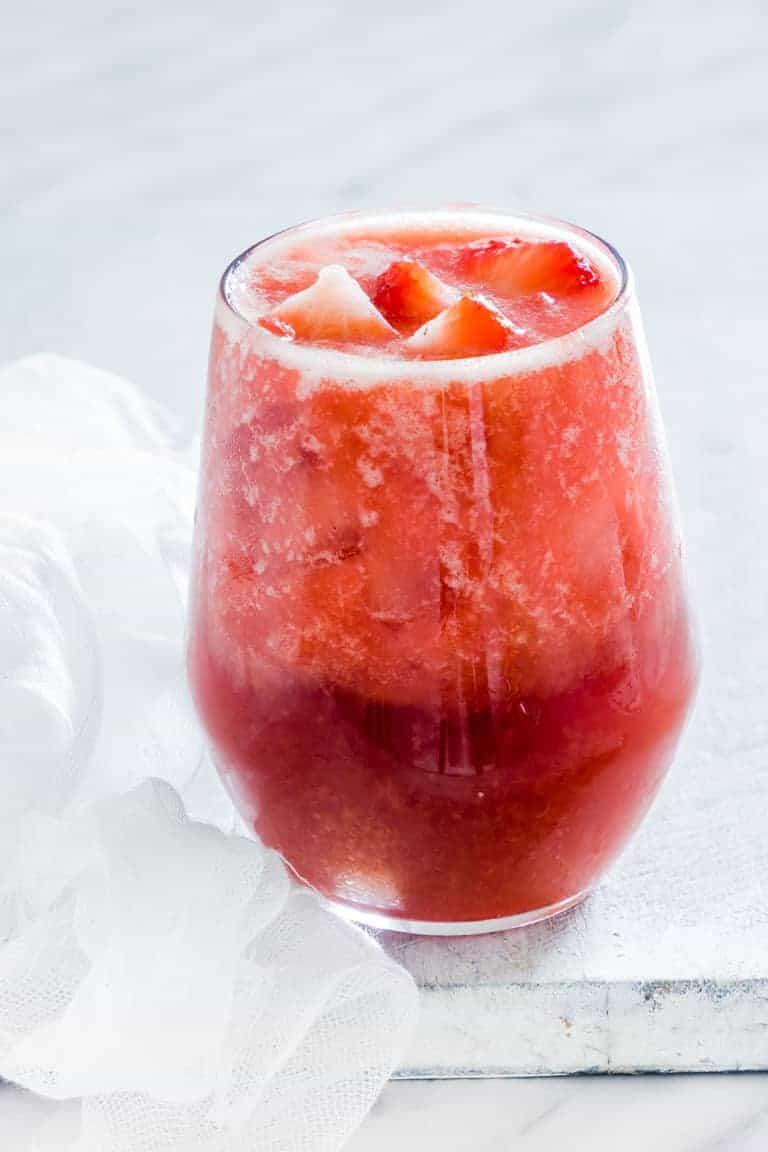 A glass of instant pot strawberry iced too on a white table