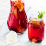 a jug and glass of non alcoholic sangria