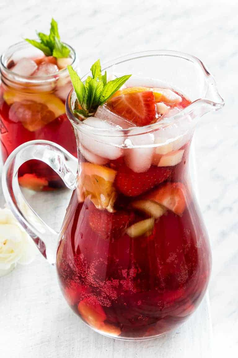 A pitcher and glass of non alcoholic sangria - virgin sangria
