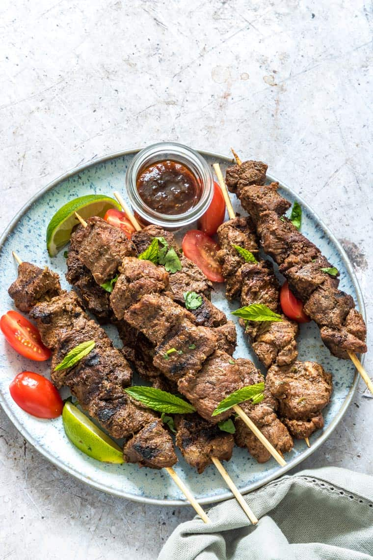 lamb kabobs served with tomatoes and a cup of dipping sauce