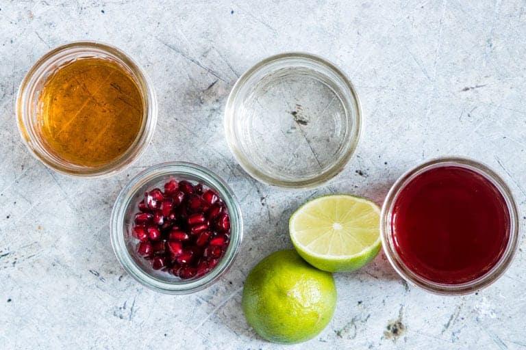 Ingredients for pomegrante martini - lime, pomegranate, vodka, orange liquer
