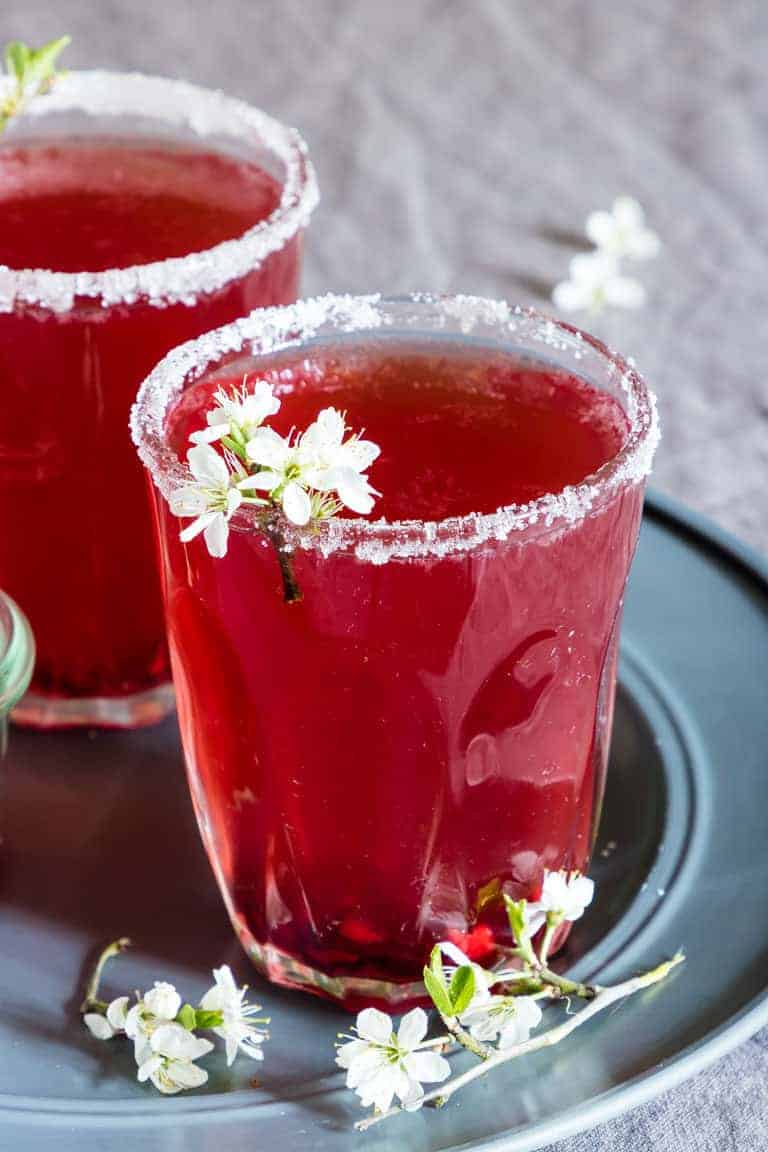 2 glasses of easy pomegranate martini on a plate