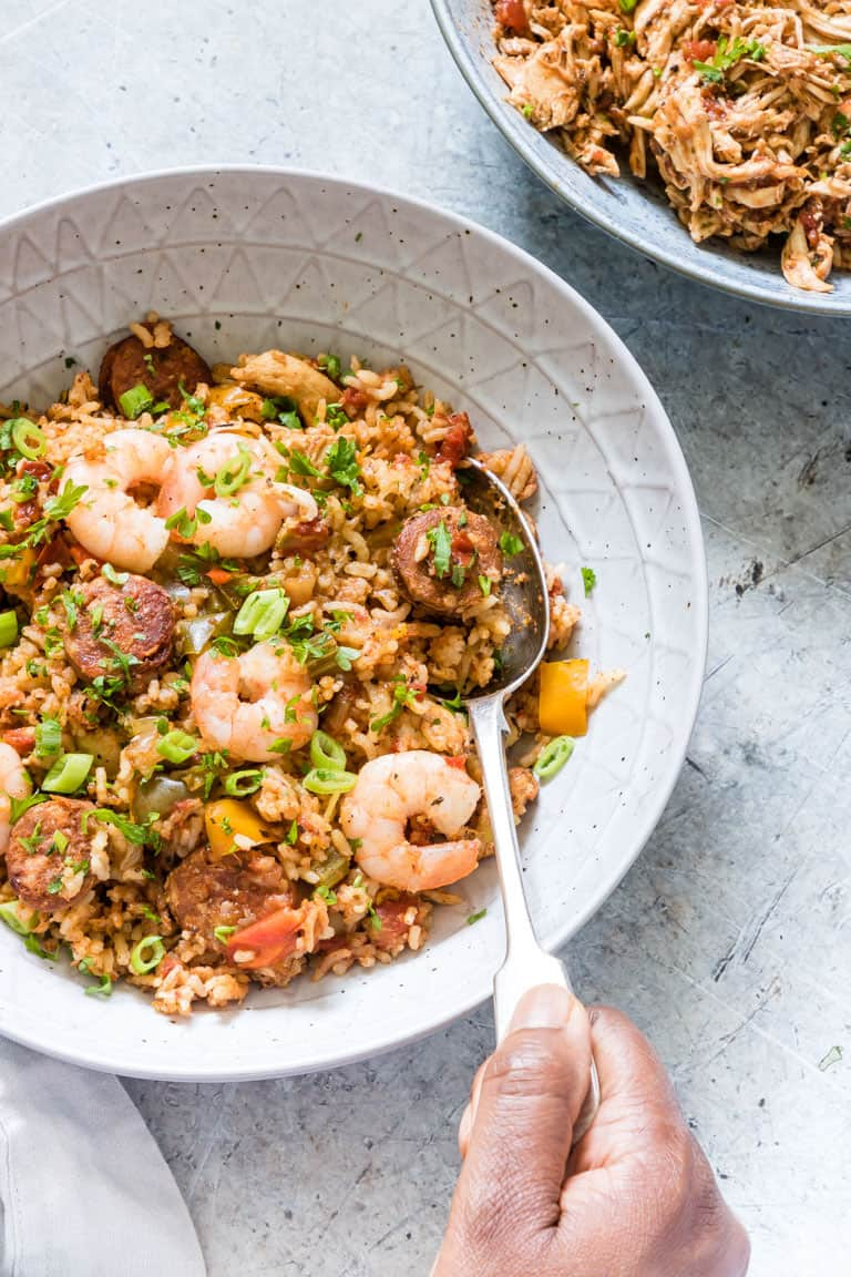 hand holding spoon digging into a bowl full of instant pot jambalaya