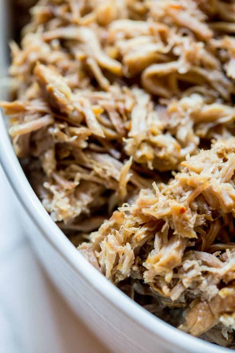 closeup of instant pot pulled pork in white casserole dish