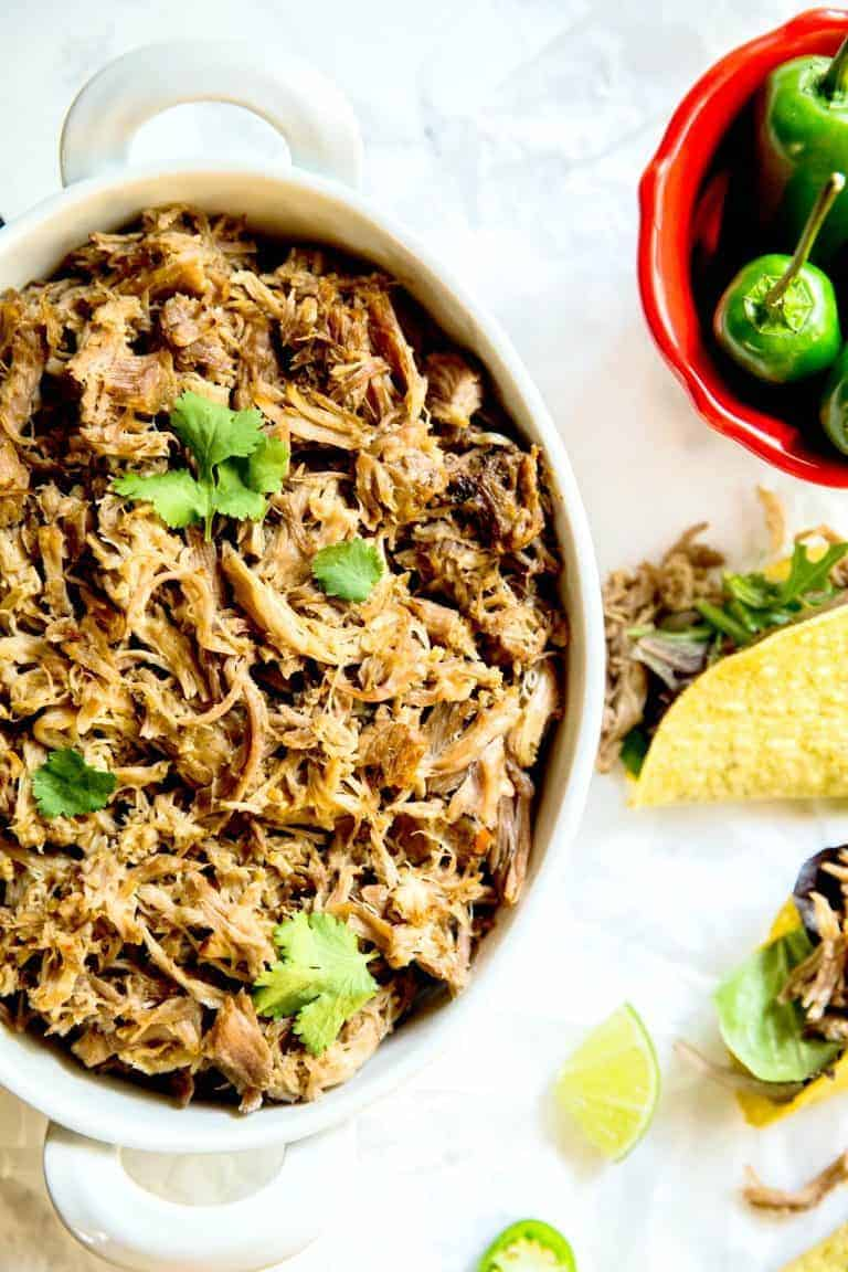 instant pot pulled pork in a large white bowl next to tacos and peppers