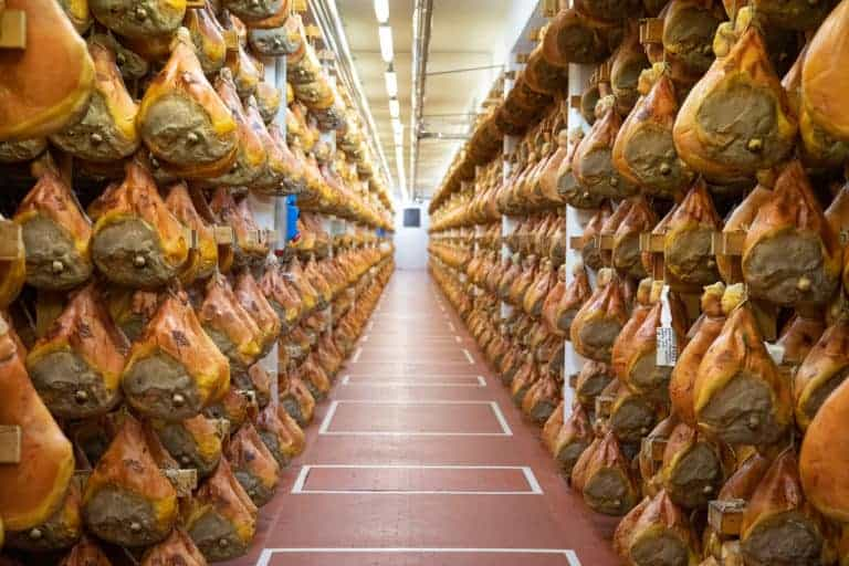 parma ham hanging in a factory
