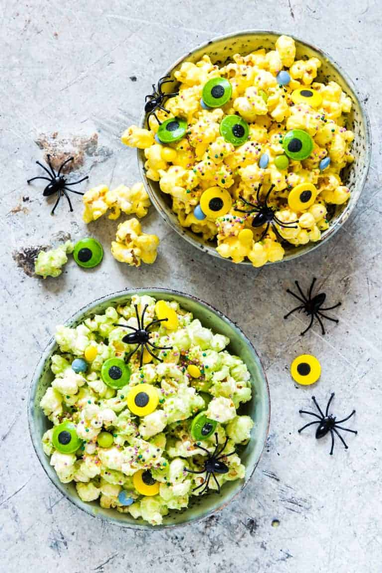 2 bowls of halloween popcorn with spiders and halloween decoration
