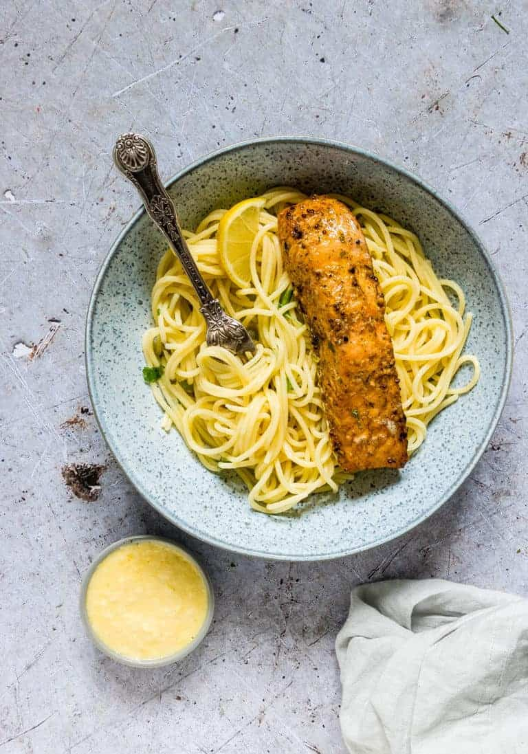 A bowl of lemon butter salmon pasta with some butter sauce.