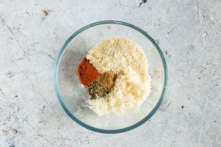 almond flour, Parmesan cheese, paprika, Herbes de Provence, Creole seasoning for the Air Fryer Pork Chops coating added to a glass mixing bowl and ready to be combined for air fryer pork chops