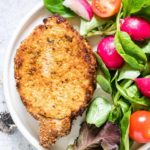 One serving of Air Fryer Pork Chops on a white dinner plate served with fresh greens and tomato salad