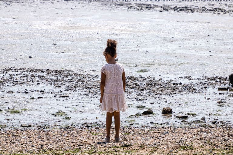 child standing on mersea island beach