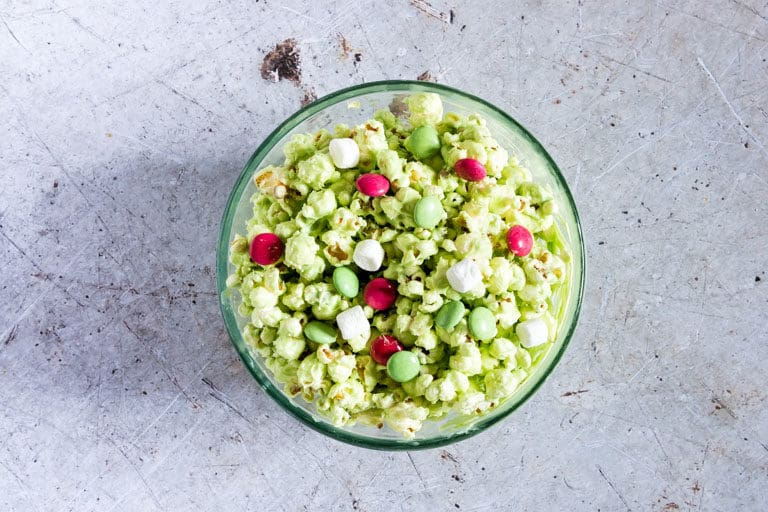 top down view of the completed Grinch Popcorn in a large glass mixing bowl