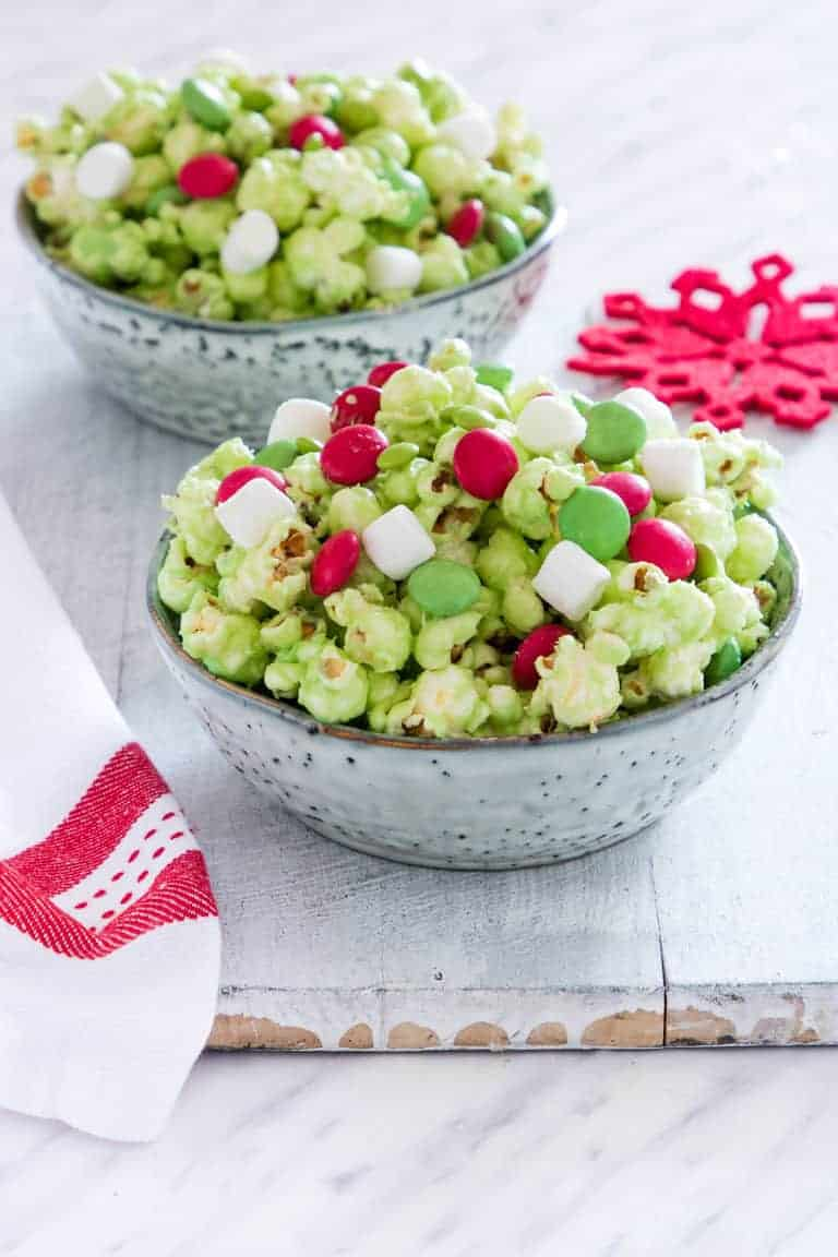 two ceramic bowls filled with Grinch Popcorn on a wooden table next to red print cloth napkin and festive red snowflake coaster