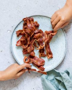 Two hands reaching for cooked strips of Crispy Air Fryer Bacon being served on a plate next to a blue cloth napkin