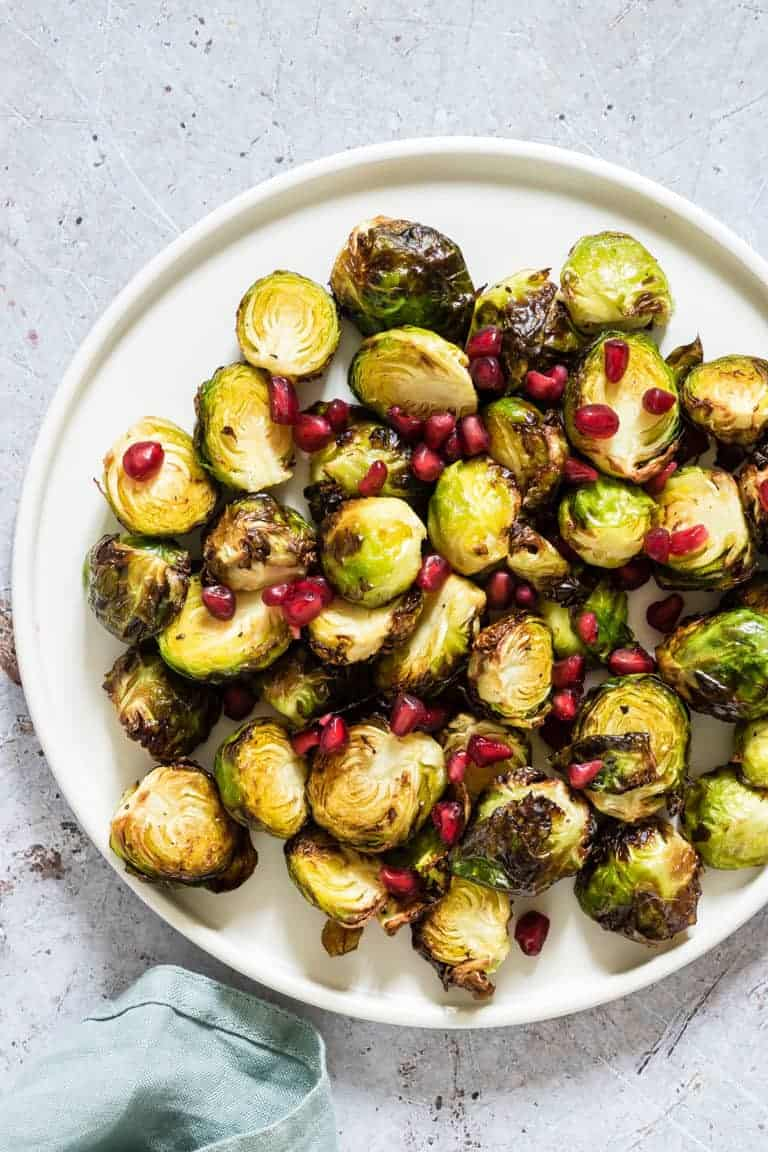 plate of air fryer brussel sprouts with pomegranate seeds