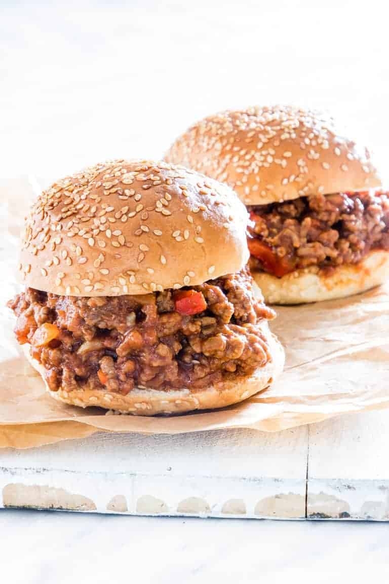 Two completed Instant Pot Sloppy Joes on a piece of parchment paper and ready to serve