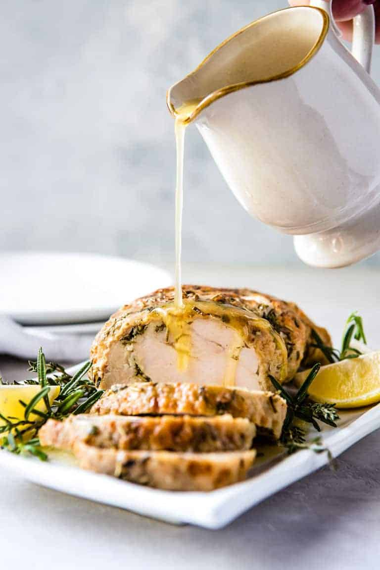 Garlic Butter Gravy being poured onto the Instant Pot Turkey Breast that is sliced and ready to serve on a white platter