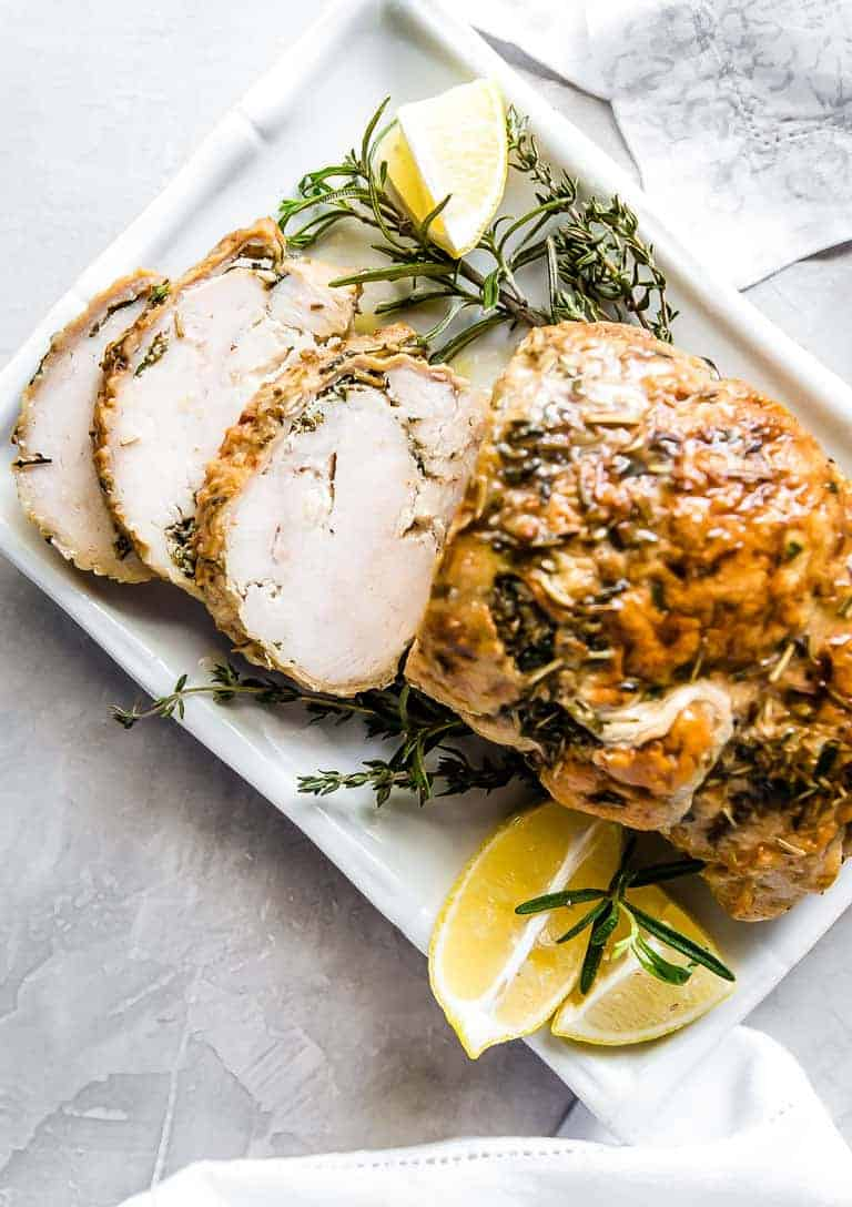 Finished Instant Pot Turkey Breast sliced and set on a white platter garnished with lemon slices and fresh herbs