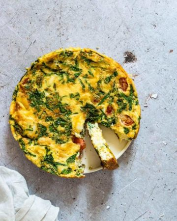 Top down view of the finished Smoked Haddock and Spinach Frittata with one slice removed and placed next to a white cloth napkin