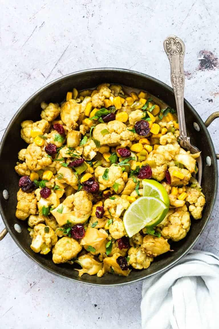 a bowl of air fryer cauliflower curry with a spoon and lime