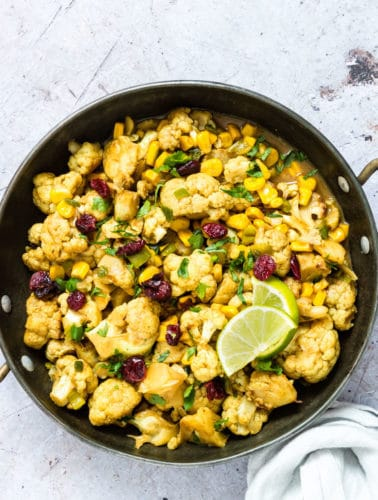 Homemade Cauliflower curry in a bowl garnished with limes
