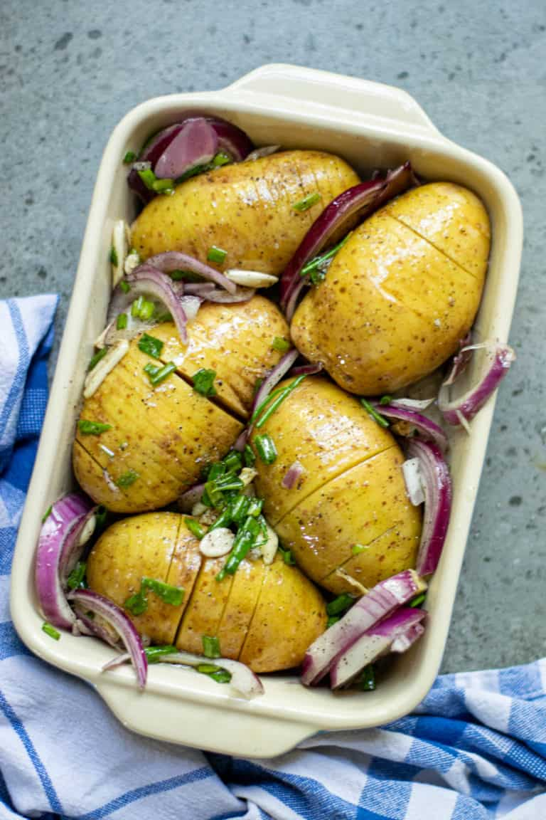 A tray full of sliced hasselback potatoes with herbs