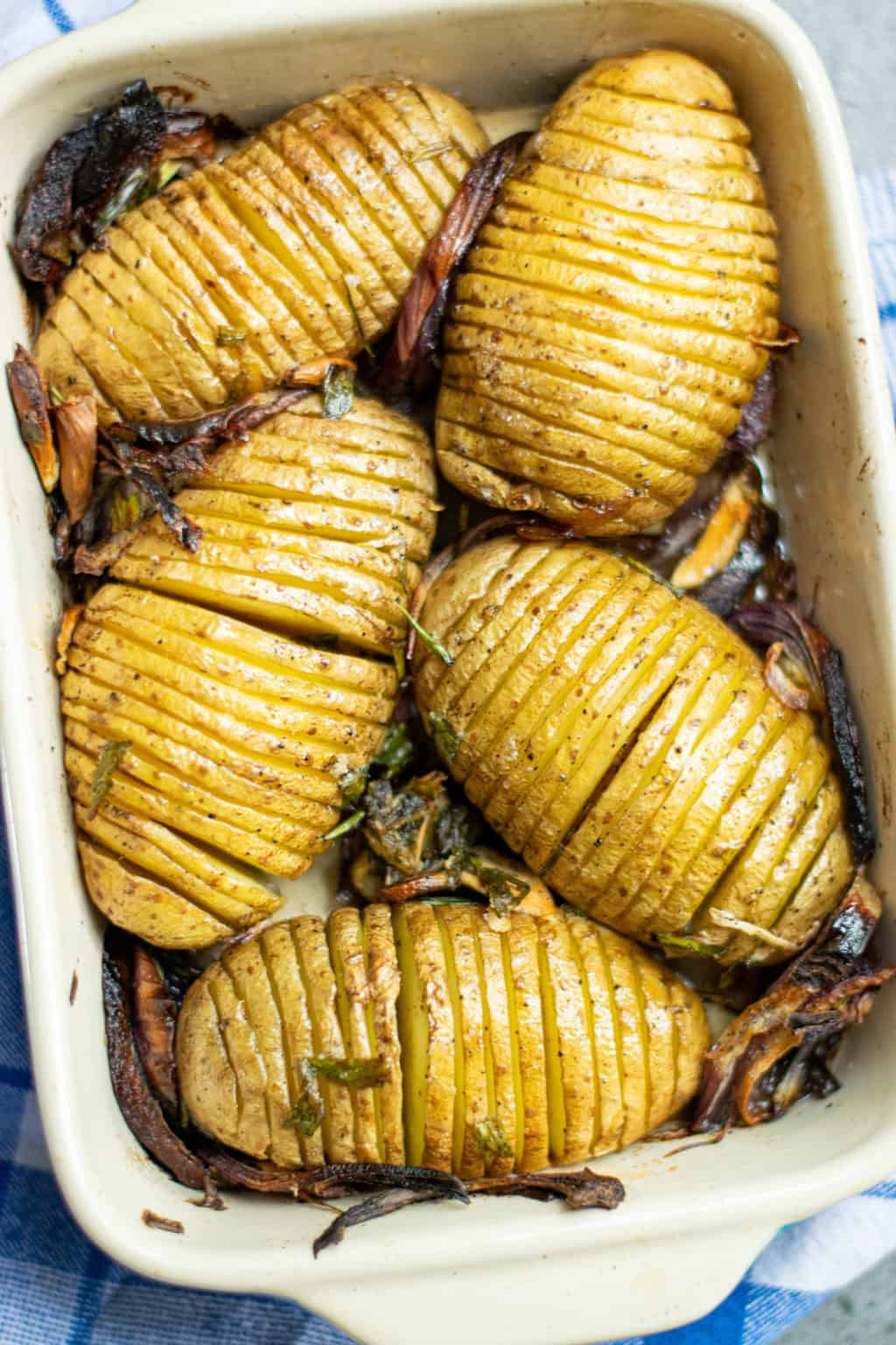 close up of crispy hasselback potatoes in a baking dish