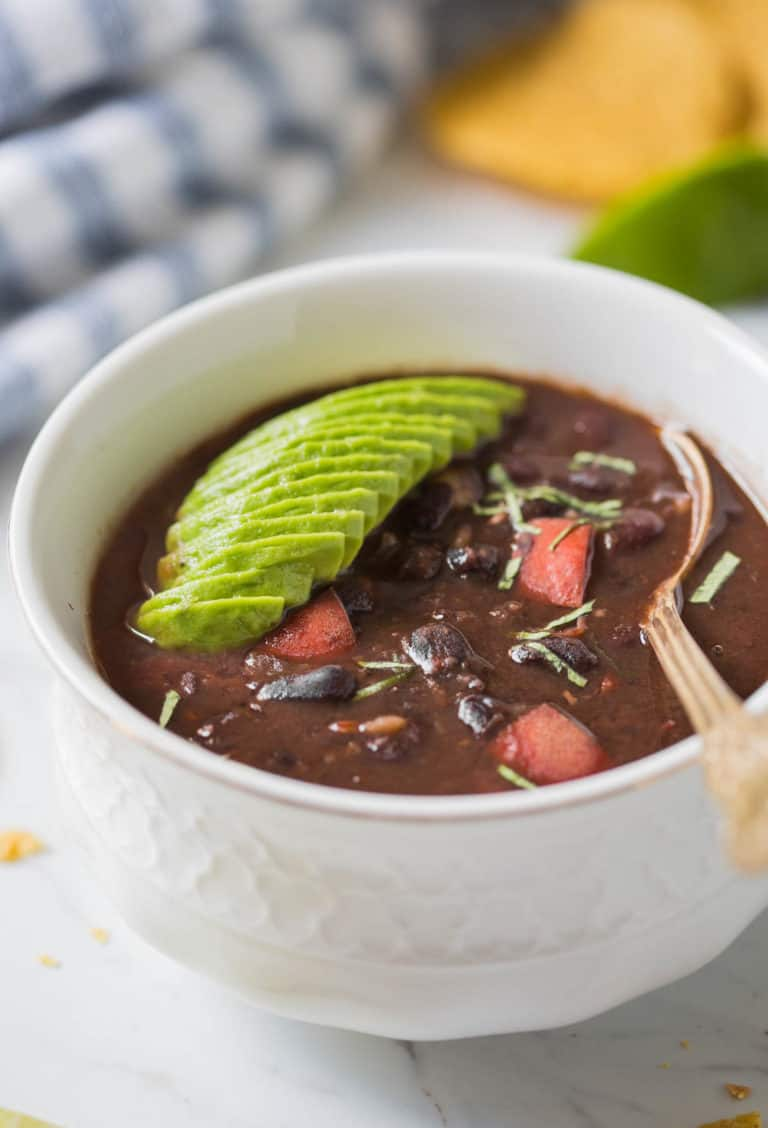 black bean soup in a white mug with a spoon and avocado slices