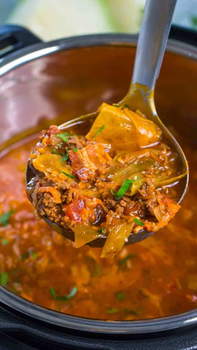 close up of a ladle filled with cabbage roll soup