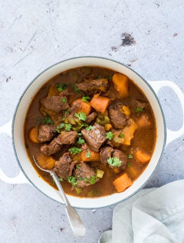 A bowl of instant pot venison stew garnished with herbs