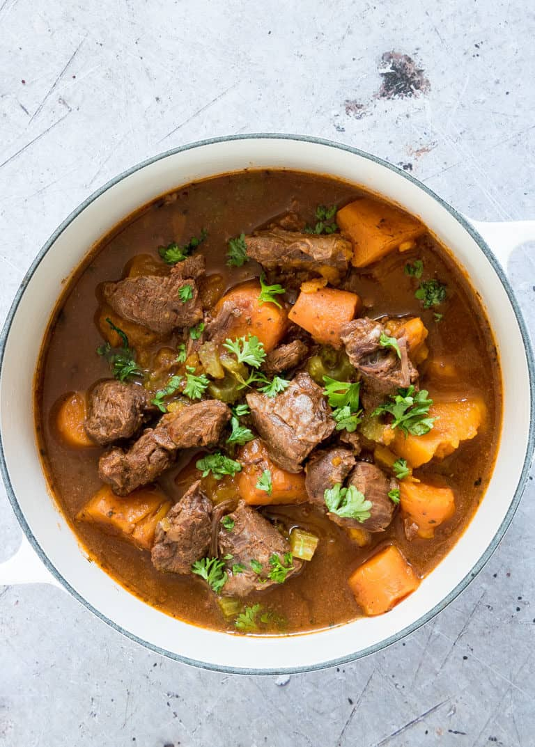 A bowl of pressure cooker venison stew with herb garnish
