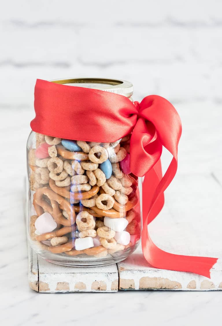 a jar of sweet and salty snack mix with a ribbon