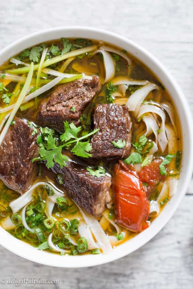 close up of vietnamese noodle soup in a white bowl