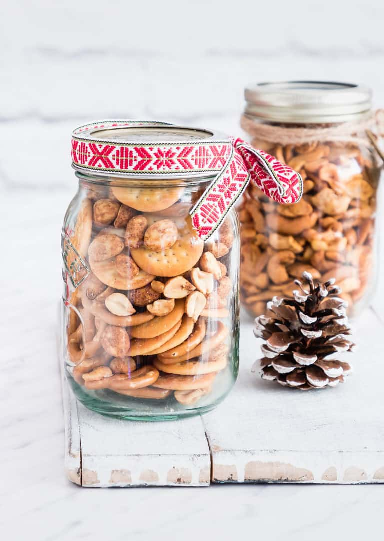 gift jars of snack mix on a table with ribbons on the jar and a pine cone