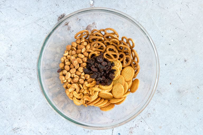 ingredients for snack mix recipe - pretzels, cheese crackers, raisins, roasted peanuts