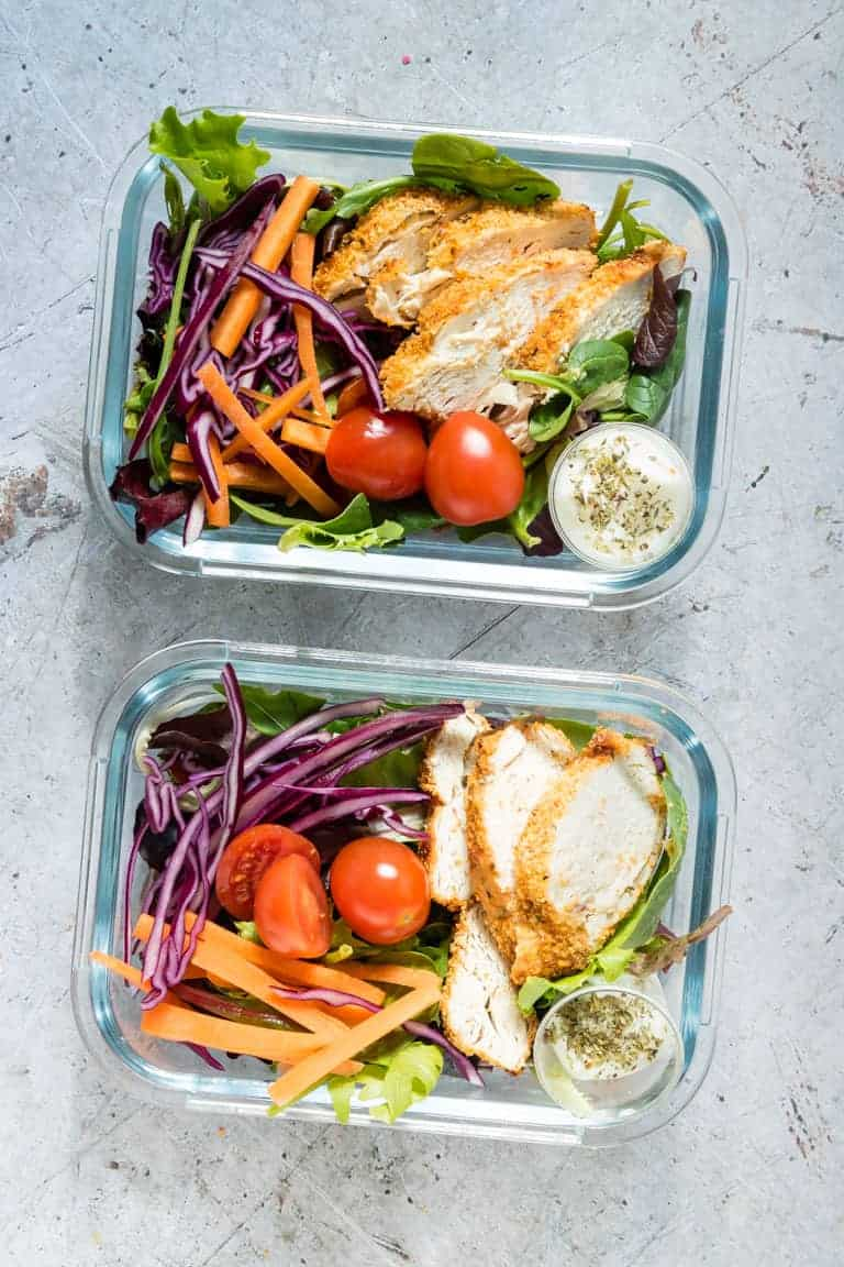 two glass meal prep containers filled with pieces of air fryer chicken breast, salad greens and sliced veggies
