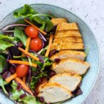 Air Fryer Chicken Breast sliced and served alongside a green salad