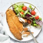 crispy air fryer fish fillet on a plate with some salad and a fork
