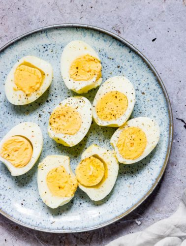 completed air fryer hard boiled eggs cut in half, seasoned with pepper and served on a blue ceramic plate