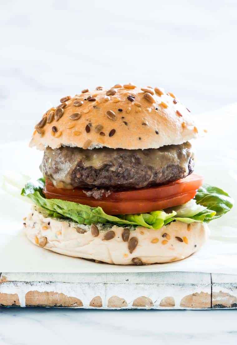 instant pot burgers on a white table with tomatoes and lettuce