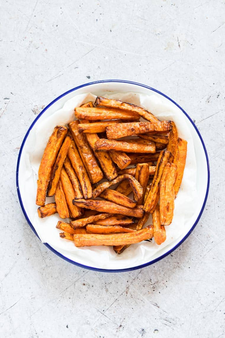 a white bowl with blue rim filled with air fryer carrot fries