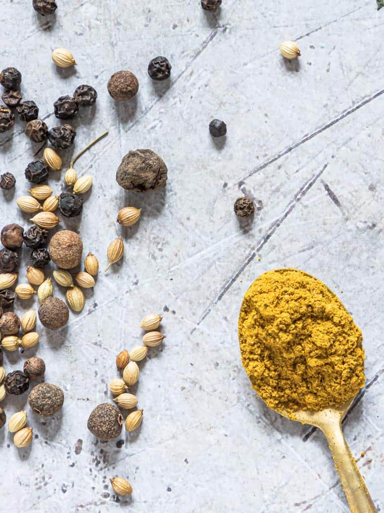 a spoonful of Jamaican curry powder next to whole spices