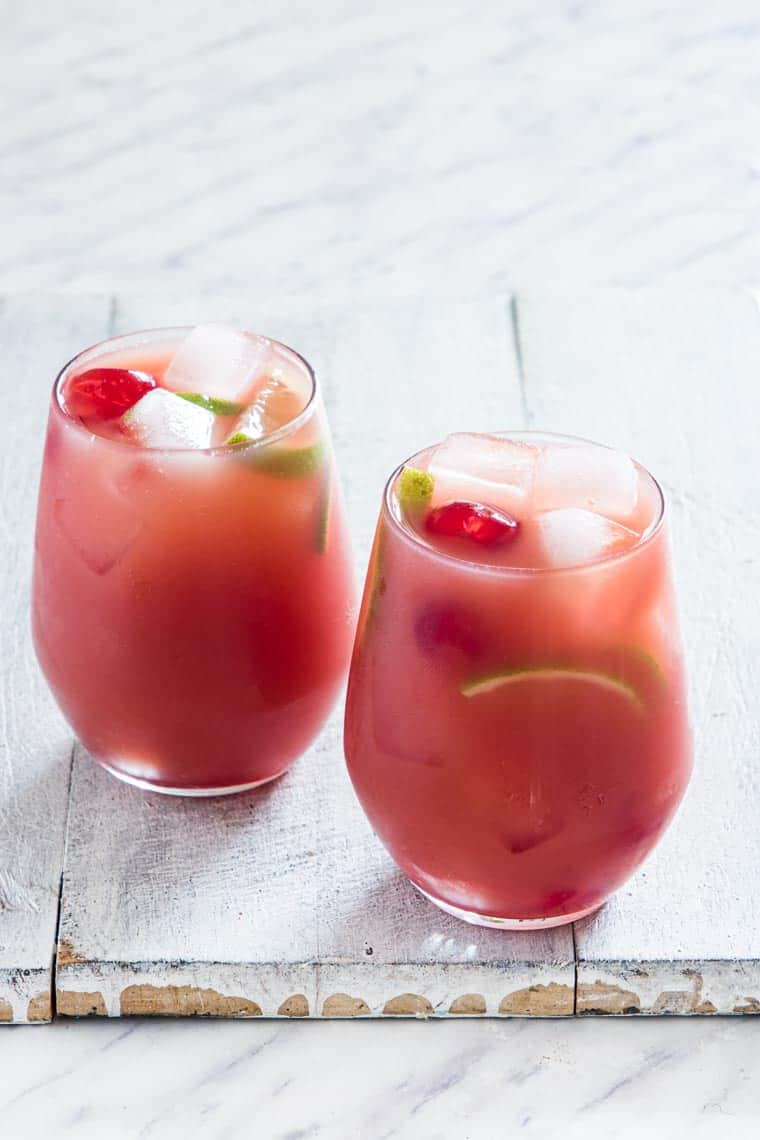 Two glasses of punch served garnishshed with lime and marachino cherries