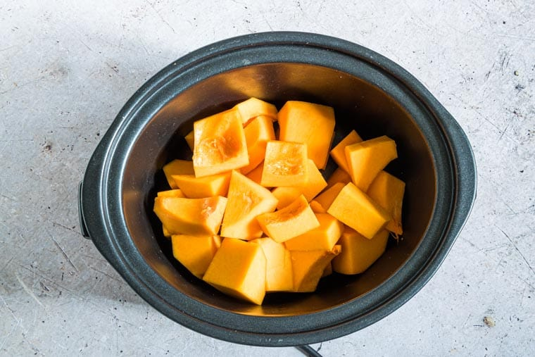 cubes of butternut squash inside the crockpot and ready to be cooked