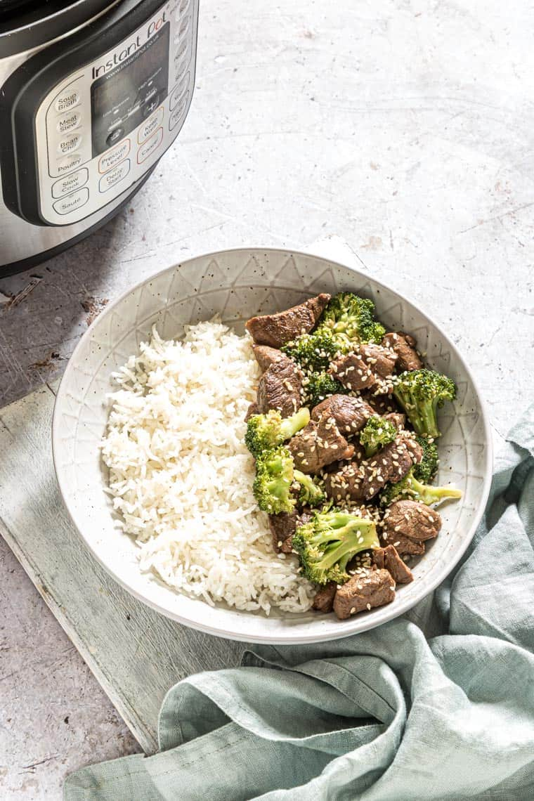 a bowl of instant pot beef and broccoli with rice set in front of the Instant Pot