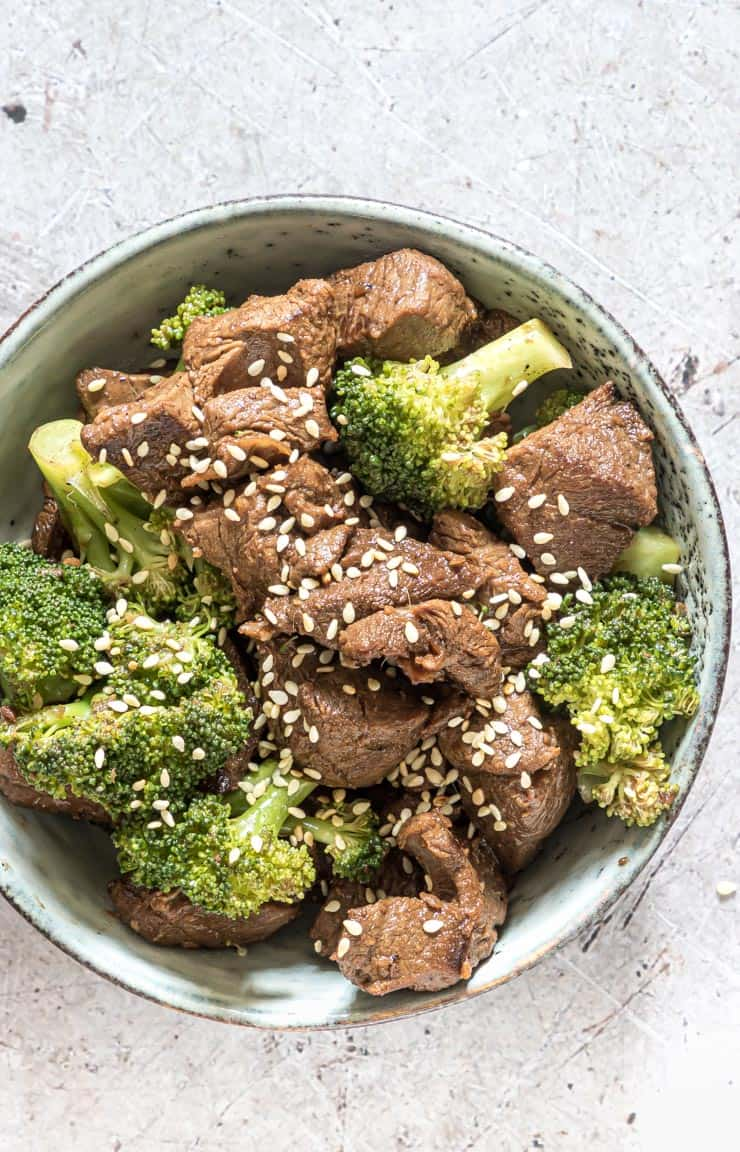 close up view of a bowl filled with instant pot broccoli beef topped with sesame seeds