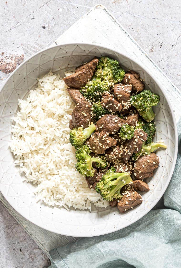 top down view of ceramic bowl with a serving of rice and instant pot broccoli beef
